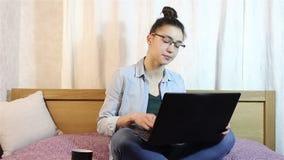En ung härlig flicka som gnider hennes ögon från trötthet som arbetar på hennes bärbar dator stock video