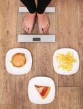 En ung härlig kvinna är på vågen Att att välja mellan potatischiper, pizza och hamburgare äta för begrepp som är sunt hälsa royaltyfri foto
