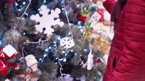 En ung härlig kvinna går runt om lagret och väljer julpynt och garneringar för att fira det nya året och Chren arkivfilmer