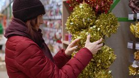 En ung härlig kvinna går runt om lagret och väljer julpynt och garneringar för att fira det nya året och Chren lager videofilmer