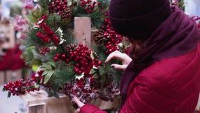 En ung härlig kvinna går runt om lagret och väljer julpynt och garneringar för att fira det nya året och Chren stock video