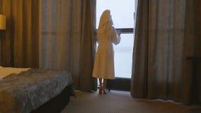 En ung härlig kvinna i ett vitt lag kommer till fönstret, öppnar gardinerna och blickarna på honom arkivfilmer