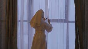 En ung härlig kvinna i ett vitt lag kommer till fönstret, öppnar gardinerna och blickarna på honom långsam rörelse lager videofilmer