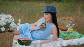 En ung härlig kvinna i en hatt och en klänning dricker lemonad från kan, medan sitta på en pläd på det gröna gräset stock video