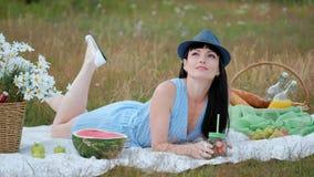 En ung härlig kvinna i en hatt och en klänning dricker lemonad från kan, medan sitta på en pläd på det gröna gräset arkivfilmer