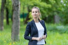 En ung härlig kvinna som bär ett affärsomslag och vita bästa leenden, i hennes händer en liten bukett av glömma-mig-nots arkivfoton