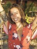 En ung härlig kvinna som svänger på en gunga av havet som tycker om koppla av på livsstil under sommarferier i paradisön arkivfoton