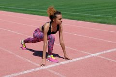 En ung härlig mörkhyad flicka i en sportig svart T-tröja och rosa gymnastikskor förbereder sig att springa i den startande linjen royaltyfri fotografi