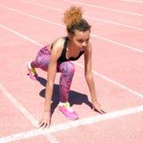 En ung härlig mörkhyad flicka i en sportig svart T-tröja och rosa gymnastikskor förbereder sig att springa i den startande linjen royaltyfria bilder