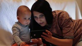 En ung härlig moder visar att något till hennes son på skärmen av en smartphone och barnet ser smartphonen arkivfilmer