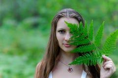 En ung härlig slavisk flicka med långt hår och den slaviska etniska klänningen täckte hennes framsida med ett ormbunkeblad Arkivfoto