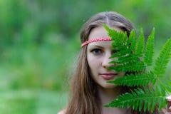 En ung härlig slavisk flicka med långt hår och den slaviska etniska klänningen täckte hennes framsida med ett ormbunkeblad Royaltyfria Bilder