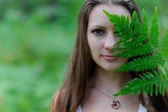 En ung härlig slavisk flicka med långt hår och den slaviska etniska klänningen täckte hennes framsida med ett ormbunkeblad Royaltyfri Foto