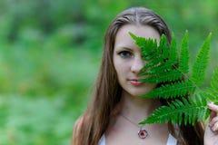 En ung härlig slavisk flicka med långt hår och den slaviska etniska klänningen täckte hennes framsida med ett ormbunkeblad Arkivbilder