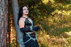 En ung häxa i svart kläder kedjas fast till ett träd halloween royaltyfri foto