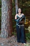 En ung häxa i svart kläder kedjas fast till ett träd halloween arkivbilder