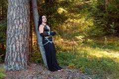 En ung häxa i svart kläder kedjas fast till ett träd halloween Se mer i min portfölj royaltyfria foton