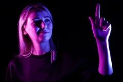 En ung h?rlig flickablondin markerade i bl?tt, och rosa p? sidorna lyfter hennes hand till ?verkanten och trycker p? p? maktknapp arkivfoton