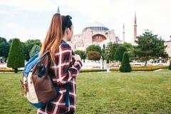 En ung handelsresandeflicka med en ryggsäck i den Sultanahmet fyrkanten bredvid den berömda Aya Sofia moskén i Istanbul i Turkiet royaltyfria foton
