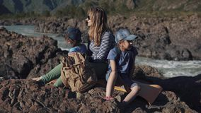 En ung handelsresandemum sitter på kanten av en klippa nära en bergflod med hennes barn Familj av turister stock video