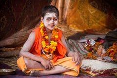 En ung hinduisk präst på Kumbhaen Mela i Indien Fotografering för Bildbyråer