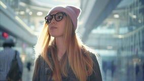 En ung hipster kvinnlig användande app på smartphonen i den stora gallerian arkivbilder