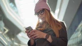 En ung hipster kvinnlig användande app på smartphonen i den stora gallerian arkivbild