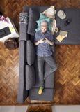 En ung hipster som l?gger i soffa i hans rum Anv?nda Smartphone f?gels sikt f?r ?ga; sikt fr?n ovann?mnt royaltyfria bilder