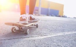 En ung hipsterflicka rider en skateboard Flickaflickvänner f Royaltyfri Foto