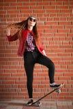 En ung hipsterflicka rider en skateboard Flickaflickvänner f Arkivbilder