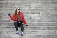 En ung hipsterflicka rider en skateboard Flickaflickvänner f Arkivfoto