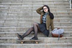 En ung hipsterflicka rider en skateboard Flickaflickvänner f Arkivbild