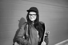 En ung hipsterflicka rider en skateboard Flickaflickvänner f Arkivfoton