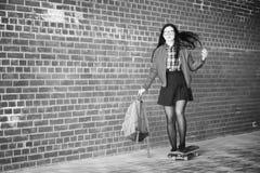 En ung hipsterflicka rider en skateboard Flickaflickvänner f Royaltyfri Fotografi