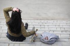 En ung hipsterflicka rider en skateboard Flickaflickvänner f Royaltyfri Bild