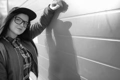 En ung hipsterflicka rider en skateboard Flickaflickvänner f Royaltyfria Bilder
