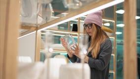 En ung hipsterkvinnlig i modeexponeringsglas väljer hem- tillbehör i lagret royaltyfri bild