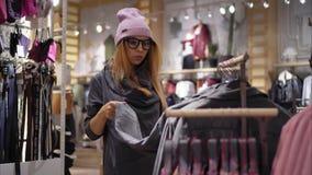 En ung hipsterkvinnlig i trendiga exponeringsglas väljer det nya omslaget hissar, exponeringsglas och metall fotografering för bildbyråer