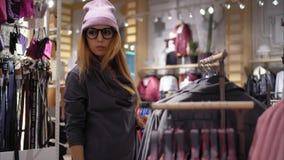 En ung hipsterkvinnlig i trendiga exponeringsglas väljer det nya omslaget hissar, exponeringsglas och metall royaltyfri foto