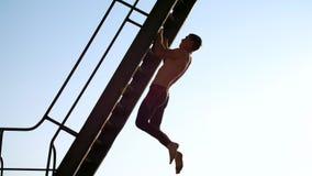 En ung idrotts- man med en kal naken torso, utför styrkaövningar, skjuter ups och att hänga på en metalltrappuppgång I a arkivfilmer