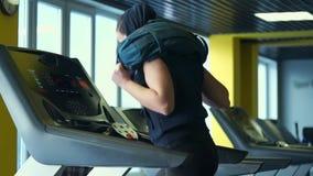 En ung idrottsman nen är förlovad på en trampkvarn som ändrar styrkan av spring lager videofilmer