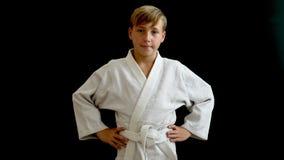En ung idrottsman nen är på flyttningen En ung man i en vit kimono tappar hans händer längs kroppen, honom står på ett mörker stock video