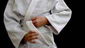En ung idrottsman nen i en vit kimono står på en mörk bakgrund Den unga mannen rymmer ett vitt bälte i hans händer, hans händer arkivfilmer