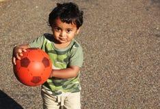 En ung indisk pojke som spelar med en röd boll Arkivbilder