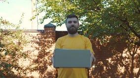 En ung kurir levererar jordlotten stock video
