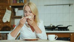 En ung kvinna äter pizza i hennes kök arkivfilmer