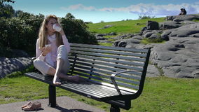 En ung kvinna använder en smartphone och dricker kaffe på bänk parkerar in långsam rörelse arkivfilmer