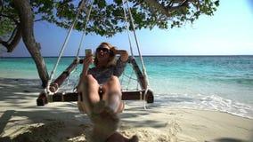 En ung kvinna använder en smartphone och tycker om att koppla av på den tropiska stranden lager videofilmer