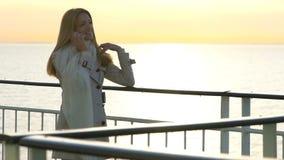 En ung kvinna använder en smartphone till däcket av eyeliner i solen långsam rörelse stock video