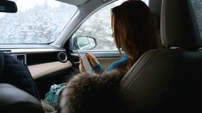 En ung kvinna använder en mobiltelefon, medan sitta framtill passagerareplatsen i en bil lager videofilmer